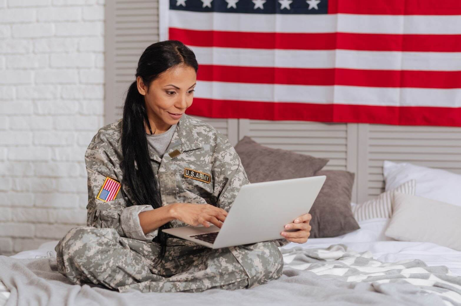 A soldier sitting on a bed using a computer